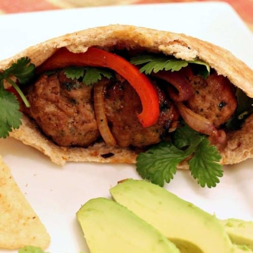 Meatballs stuffed into pita half with peppers and onions on plate with chips and sliced avocado.