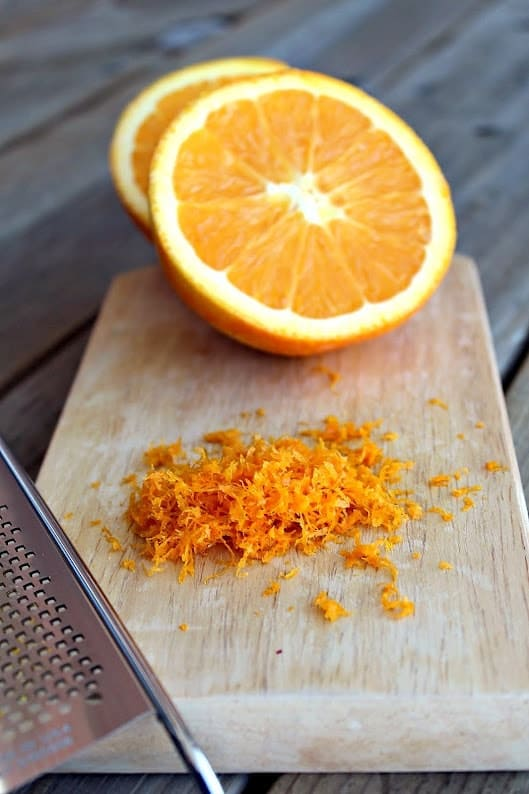 Orange halves on small cutting board with zest and zester.