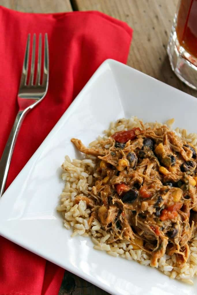 Top view of slow cooker chicken on brown rice, in a square white plate with fork and red napkin.
