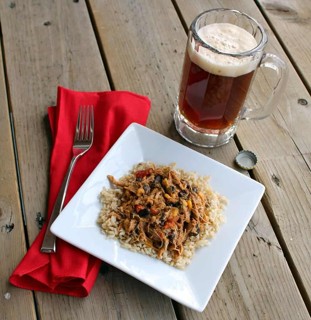 Overhead of plate with salsa chicken, red napkin with fork, clear glass mug with beer, on a wooden deck.