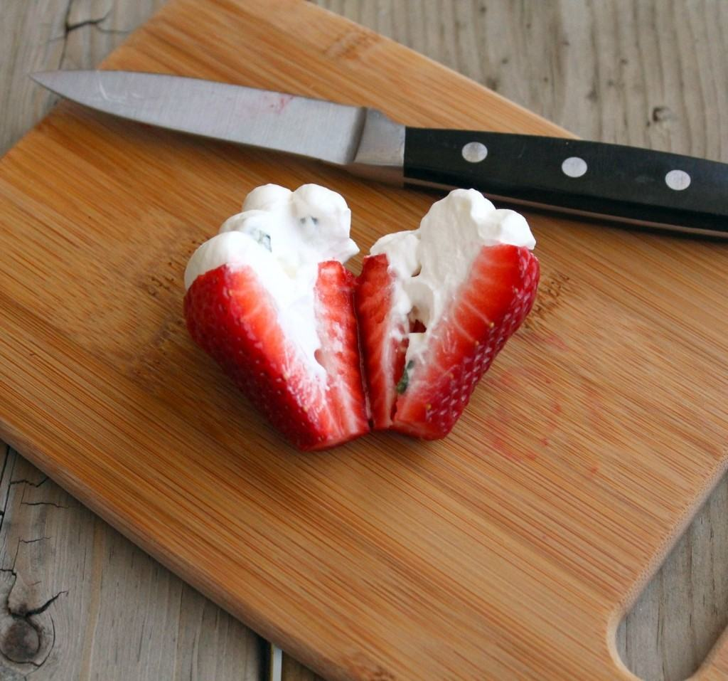Strawberry filled with whipped cream, cut open to show inside.