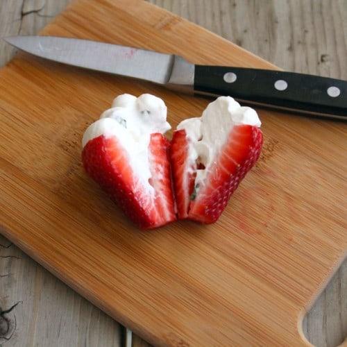 Stuffed strawberry sliced in half on cutting board.