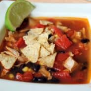 Closeup of chicken tortilla soup in square white bowl, garnished with crushed tortilla chips and wedge of lime.