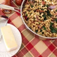 Overhead view of large skillet with pasta dish, small white plate containing Parmesan cheese and grater, on a red plaid tablecloth.