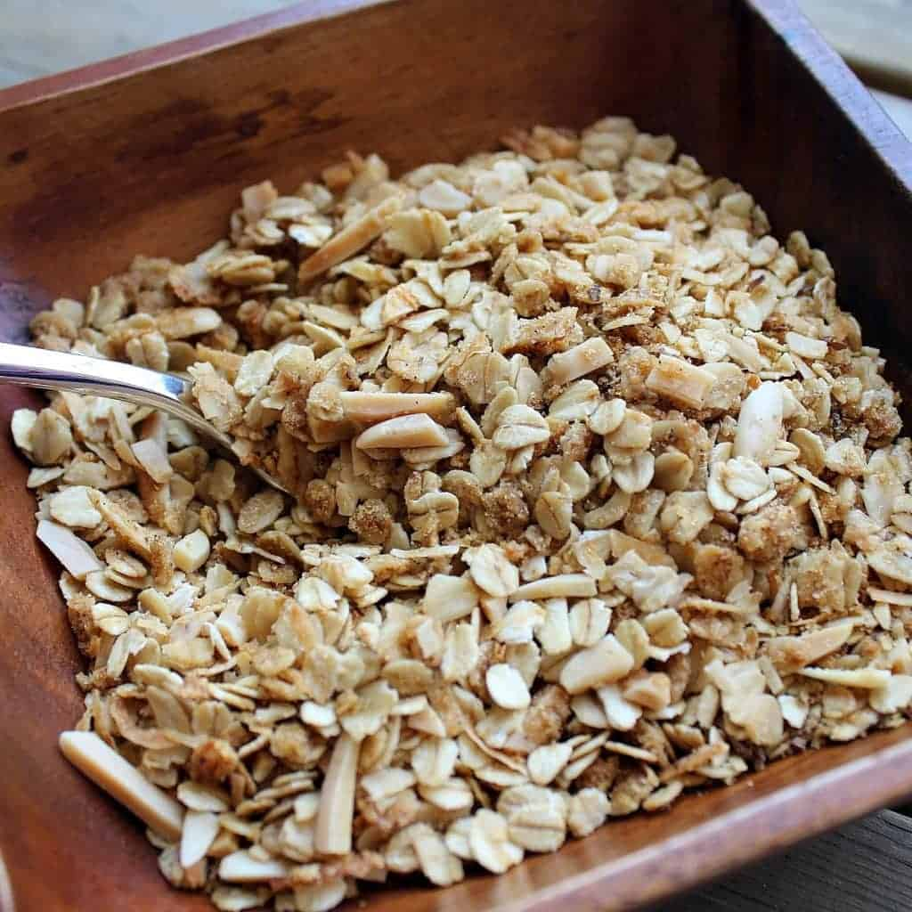 Overhead closeup of wooden bowl with granola and spoon.