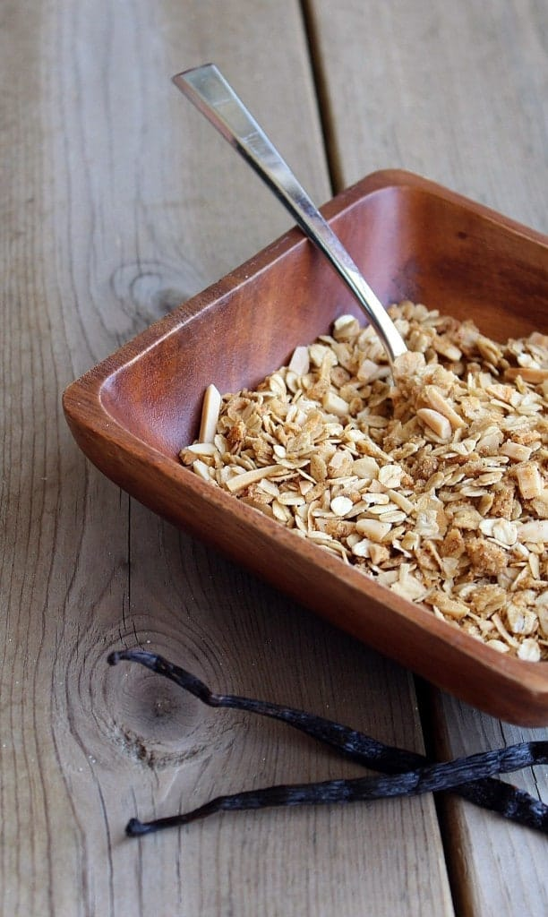Partial view of square wooden bowl containing granola with spoon. In front of bowl are two vanilla beans.