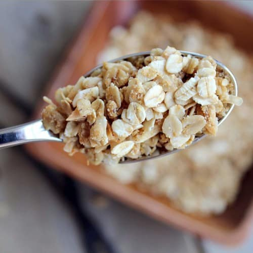 Overhead closeup of spoonful of granola, with bowl in background.