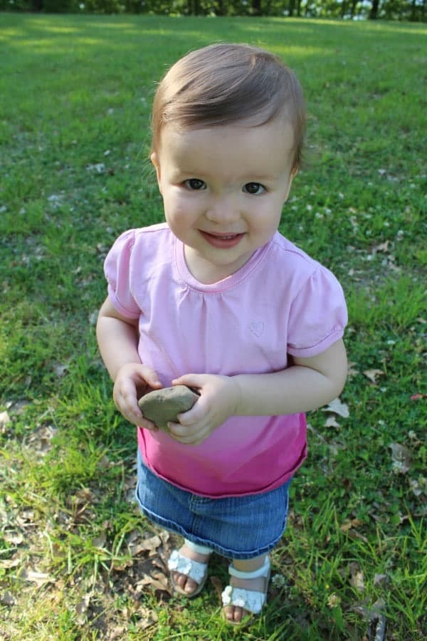 The author's adorable baby girl holding a rock.