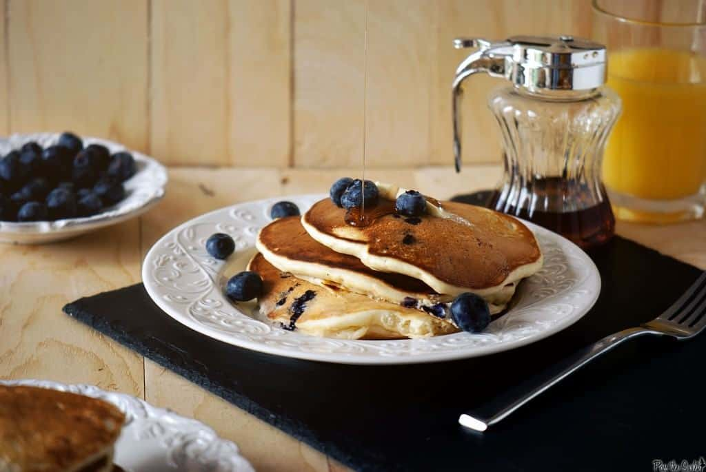 Plate of pancakes, on black placemat with fork and syrup in small pitcher. Bowl of fresh blueberries in background, along with orange juice.