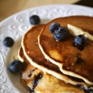 Blueberry pancakes stacked on white plate, garnished with fresh blueberries.