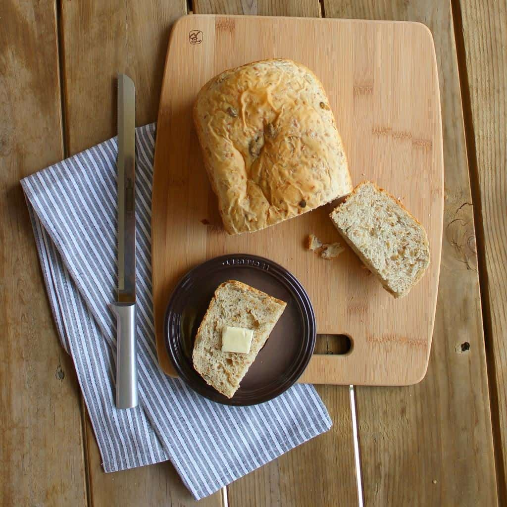 Overhead view of bread on board, plate with slice, wooden cutting board, blue striped cotton towel, and bread knife.