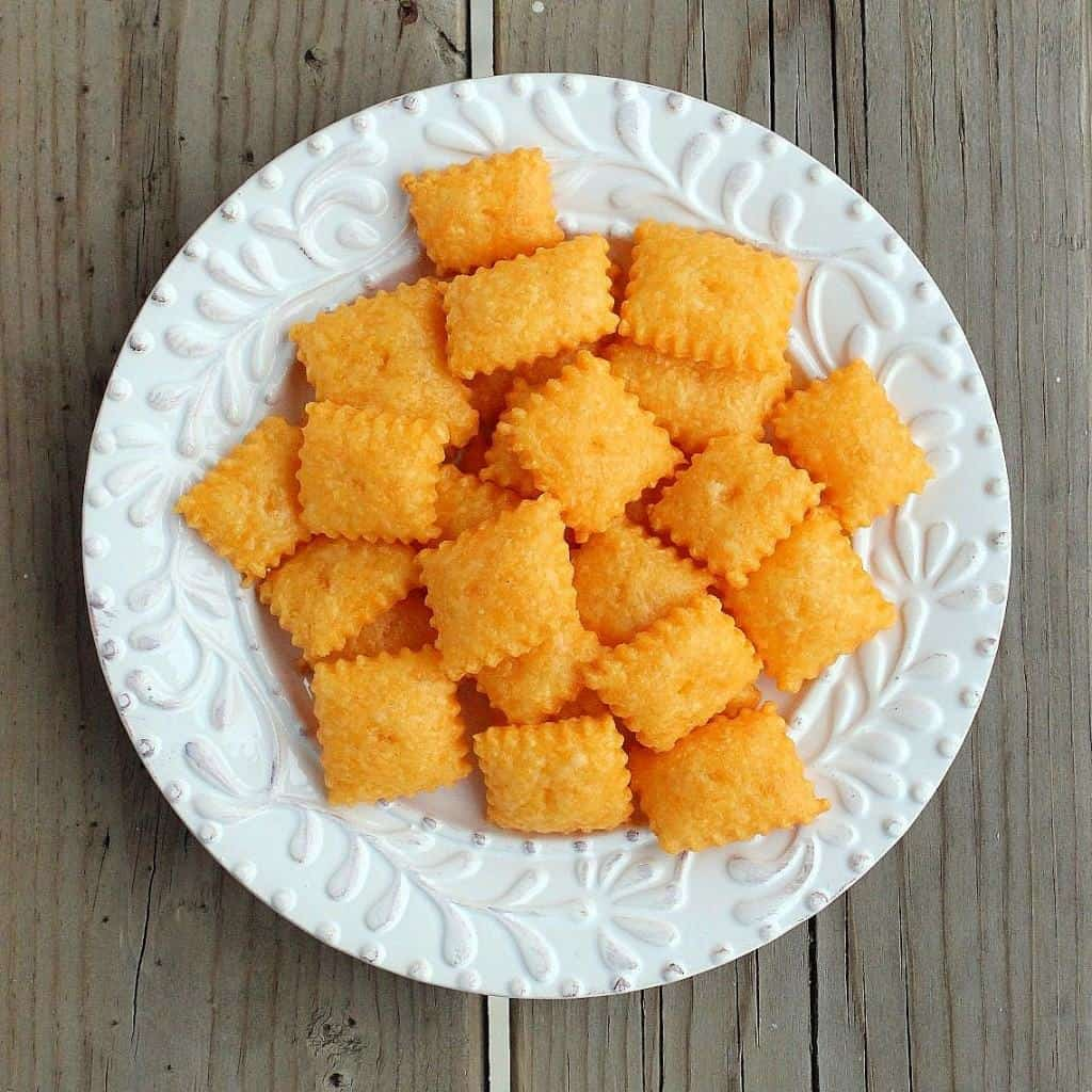 Overhead view of round white plate containing several homemade cheez-its.
