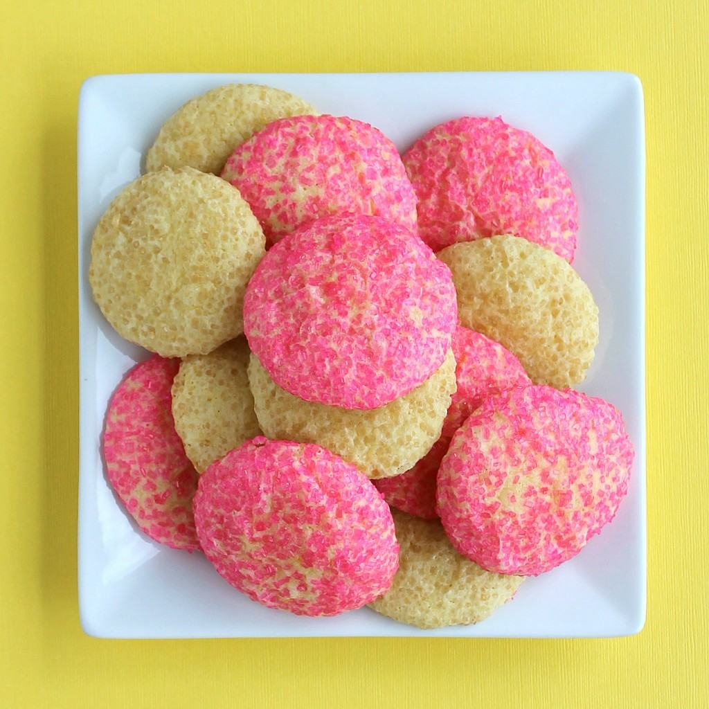 Overhead shot of white square plate containing several lemonade cookies, some pink and some yellow. Bright yellow background.