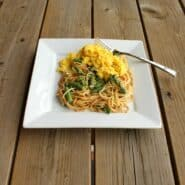 Square white plate containing a serving of pasta with asparagus and scrambled eggs.