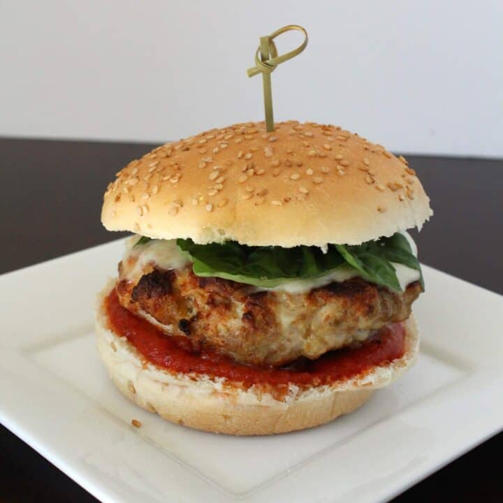 A turkey burger on a white plate, the burger has cheese on it, fresh basil, and pizza sauce.
