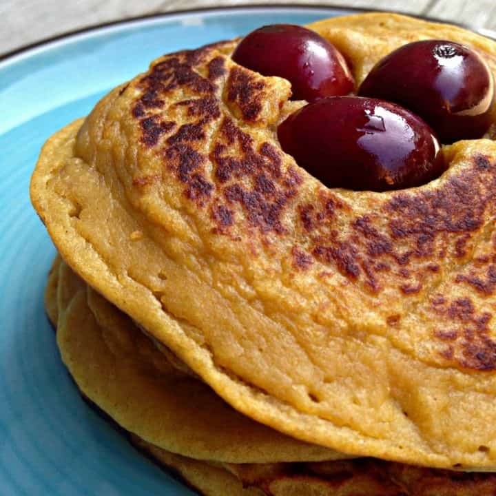 Partial image of stacked pancakes with three cherries on blue plate.