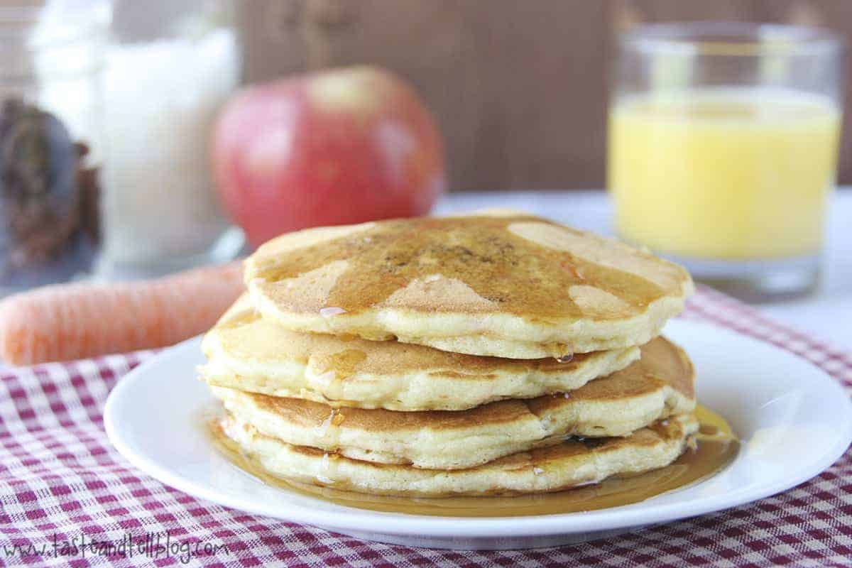 Front view of 4 pancakes drizzled with maple syrup and stacked on white plate.