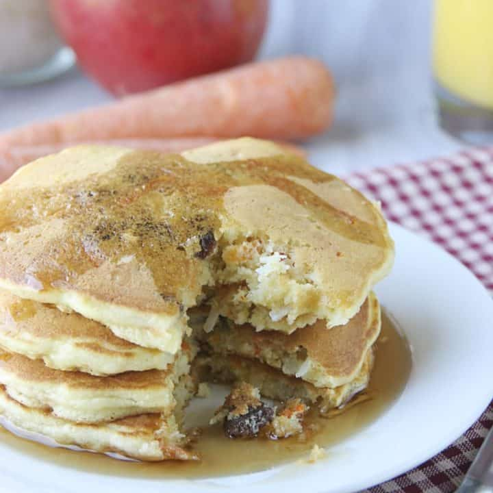 Four pancakes on white plate, with maple syrup.