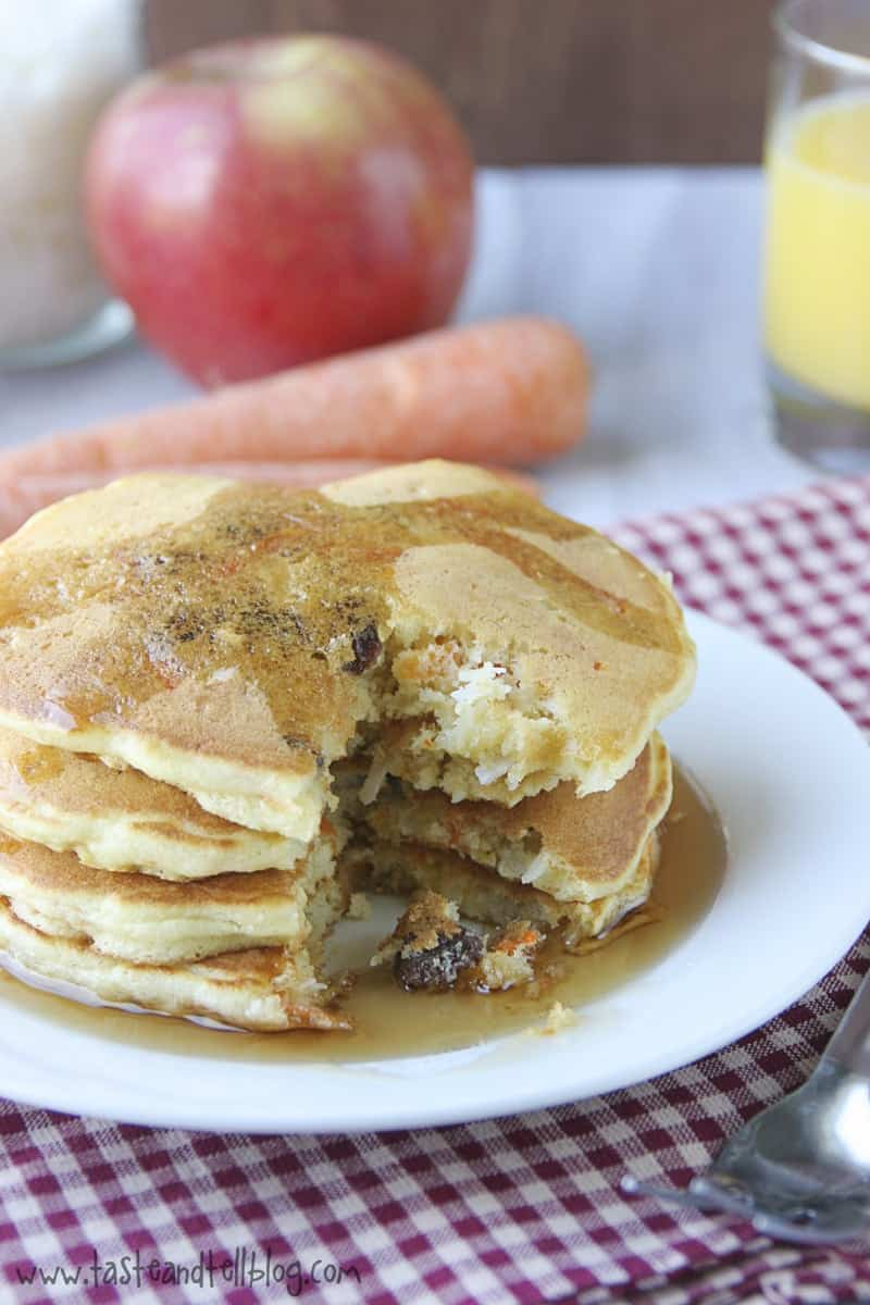 Pancakes on plate with wedge removed. Carrot and apple in background.