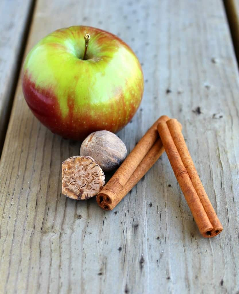 An apple, two cinnamon sticks, and a couple of nutmegs on a wooden surface.