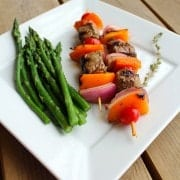 2 beef skewers on square white plate, with asparagus spears and sprig of thyme.