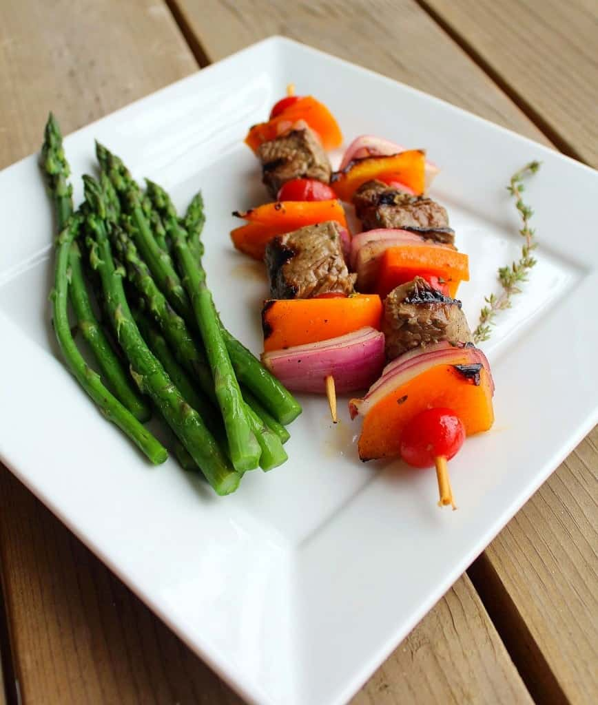 Two kabobs on square white plate, with asparagus spears and sprig of thyme.
