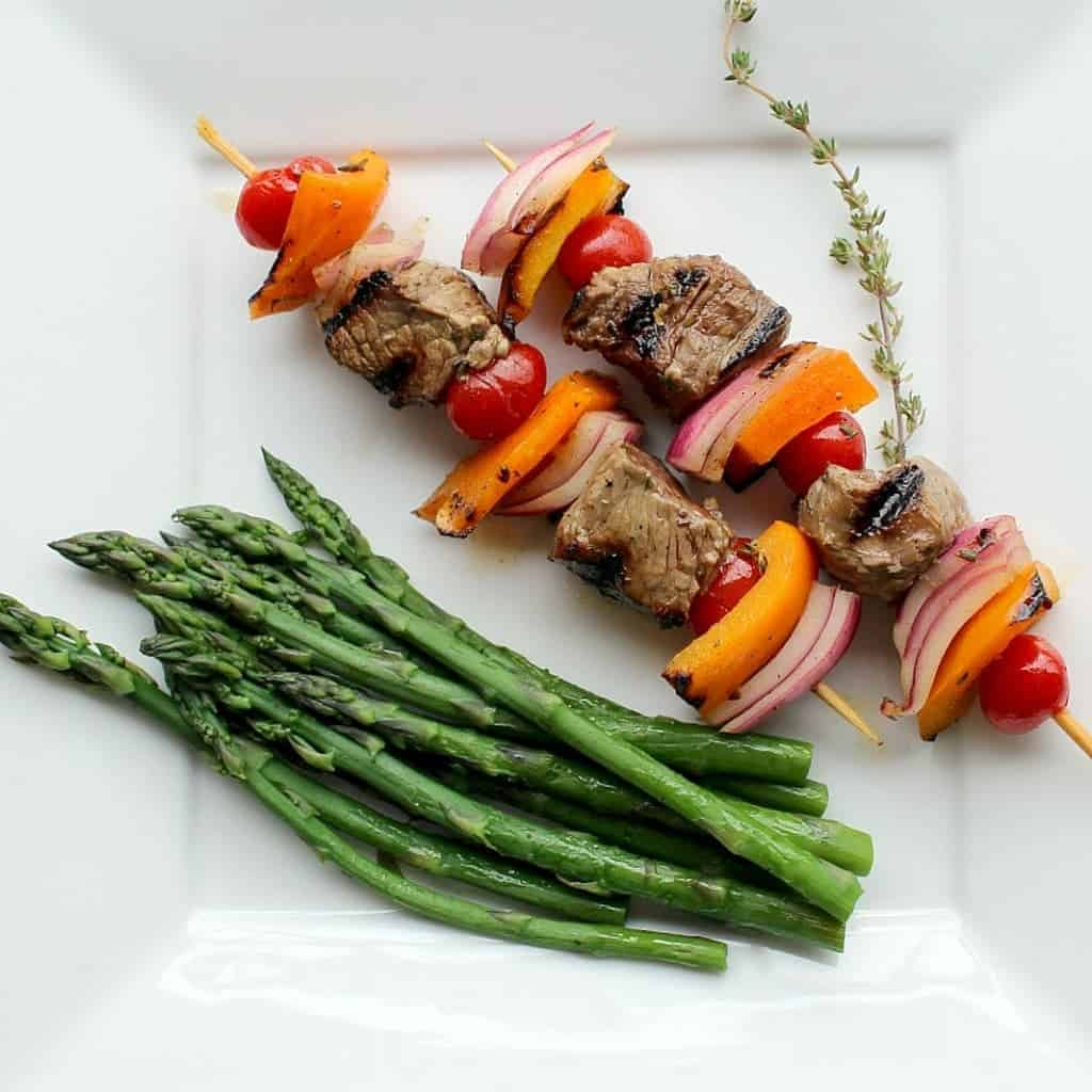 Two kabobs on square white plate with asparagus spears and sprig of thyme.