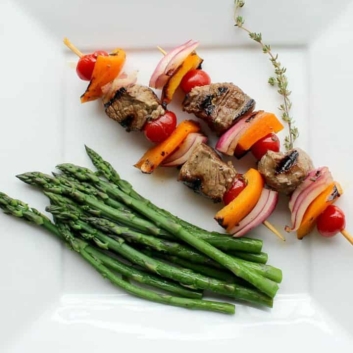 2 skewers on square white plate, with asparagus spears and sprig of thyme.