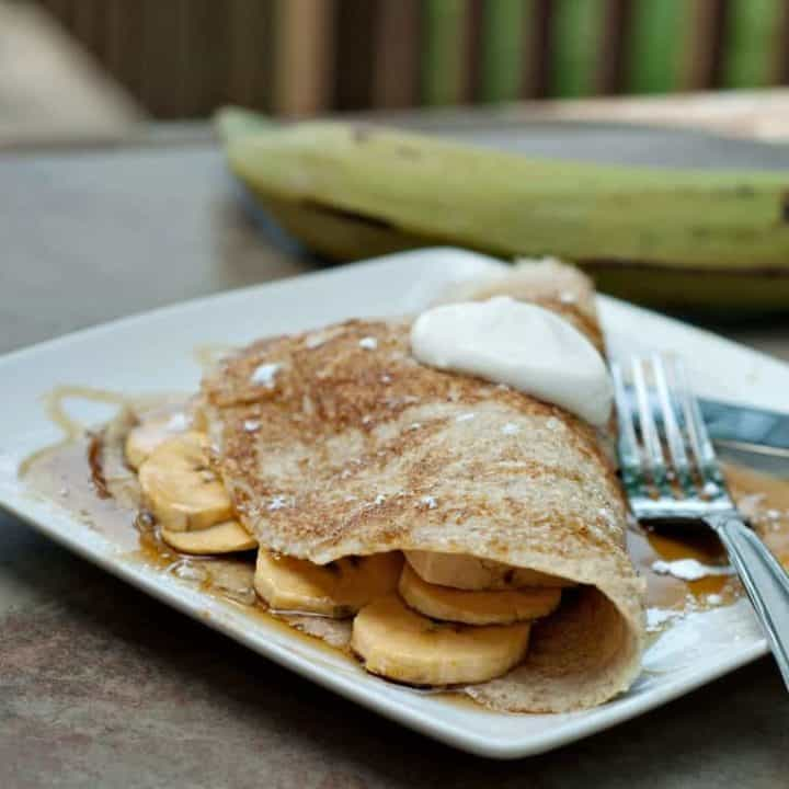 Pancake folded around plantain filling on square white plate.