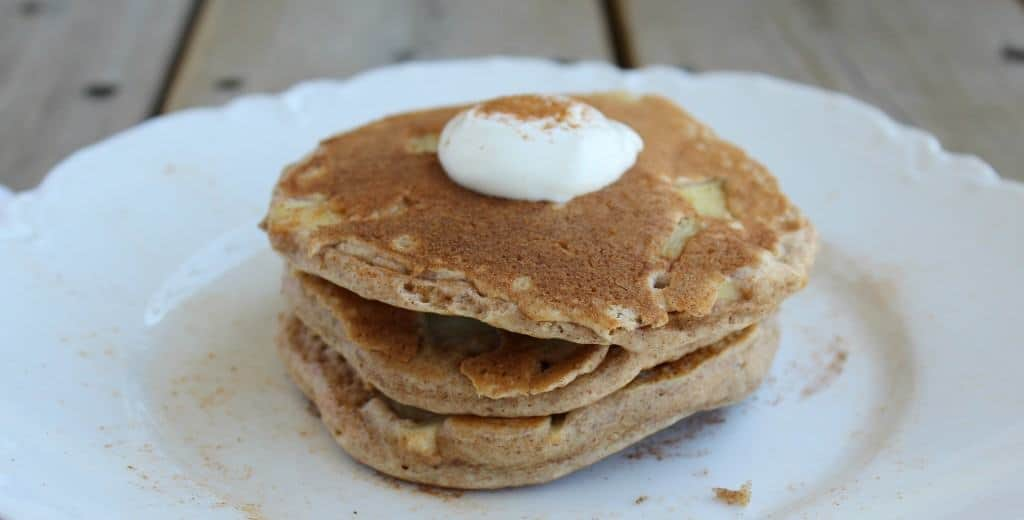 Front view of three stacked pancakes on white plate.