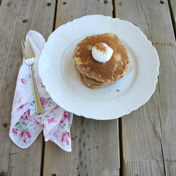 Pancakes on a white plate on a wooden surface.