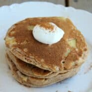Three stacked pancakes on white plate, topped with yogurt and cinnamon.