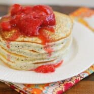 Stack of pancakes topped with juicy red strawberries.