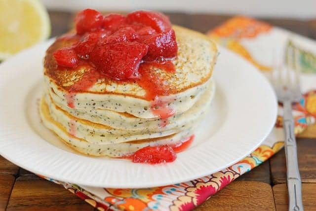Stack of four pancakes topped with strawberries on white plate.