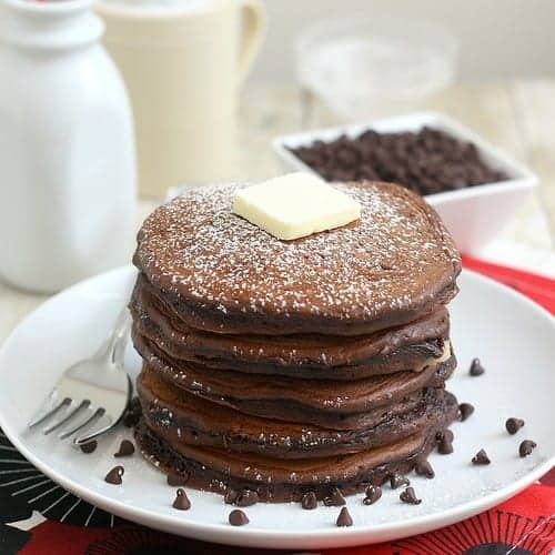 A stack of pancakes, topped with a square of butter, on round white plate, with mini chocolate chips surrounding the pancakes.