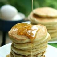 A stack of corn cakes with syrup drizzling on the top.