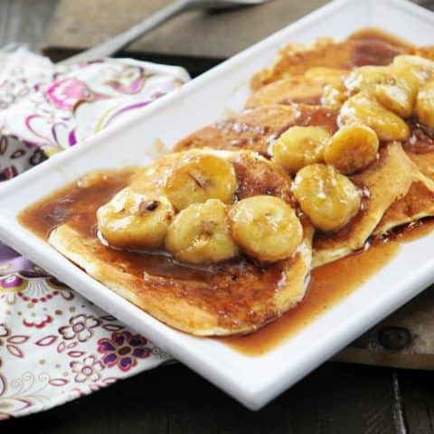 Rectangular white platter with pancakes and bananas in rum sauce.