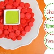Many tiny red pancakes surrounding a small square bowl of bright green dip.