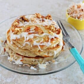 Stack of pancakes with glaze and coconut, on clear glass plate with decorative fork.