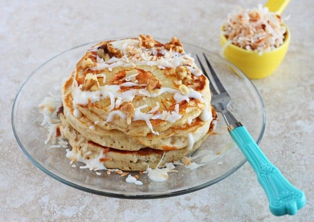 Stack of three pancakes, drizzled with glaze and topped with pecans, on clear glass plate, with decorative fork.