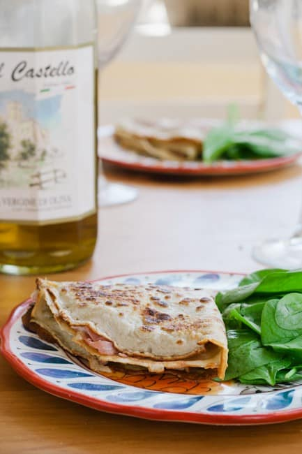 Folded crepe on plate, with wine bottle in background.
