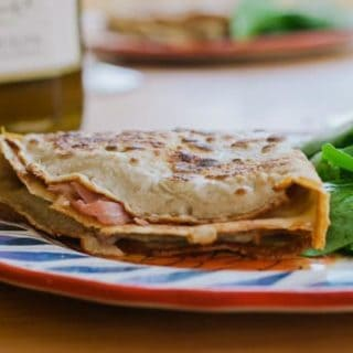 Folded and filled crepe on decorative plate, with salad.