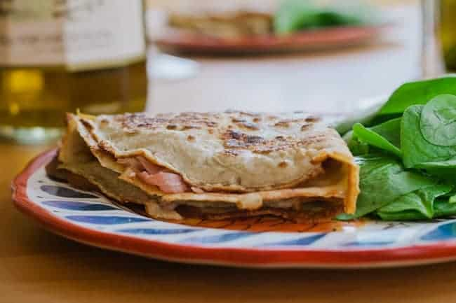 Folded and stuffed buckwheat crepe on decorative plate, along with spinach leaves.