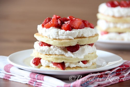 Front shot of 3 pancakes stacked and layered with whipped cream and strawberries.