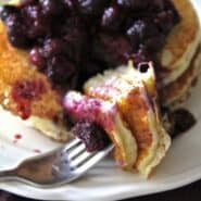 Forkful of pancakes topped with blueberry sauce.