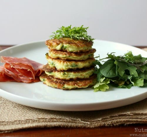 Front view of white plate containing pancakes, dressing, greens, and meat.