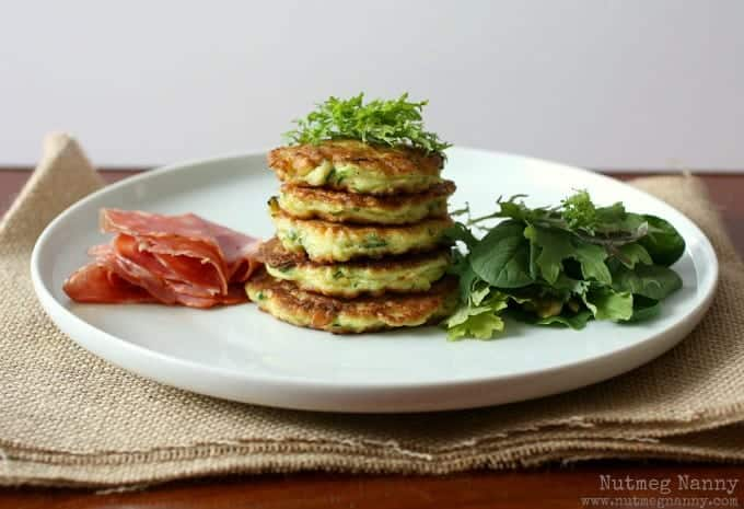 Front view of round white dinner plate containing stack of five squash pancakes, garnished with fresh greens and capicola, on a burlap placemat.