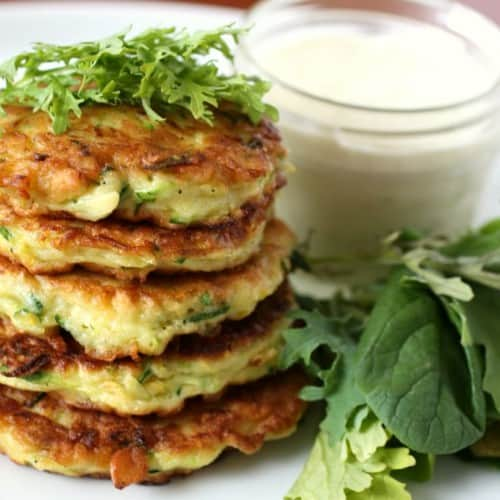 Stack of summer squash pancakes garnished with herbs.