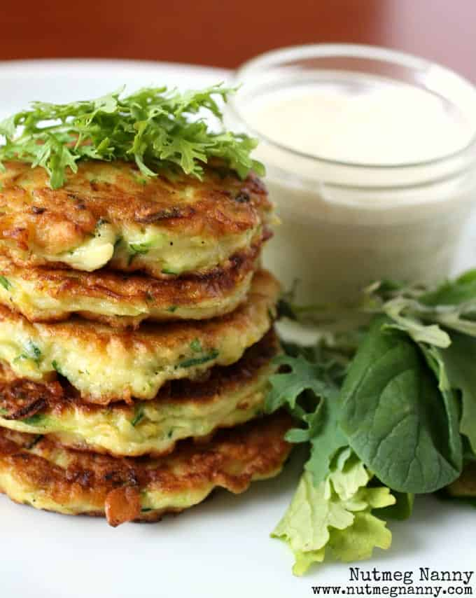 Close up front view of pancake stack with small clear jar of goat cheese dressing, and greens.
