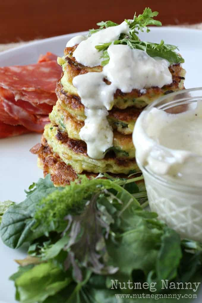 Closeup of pancake stack drizzled with dressing on plate with greens and meat.
